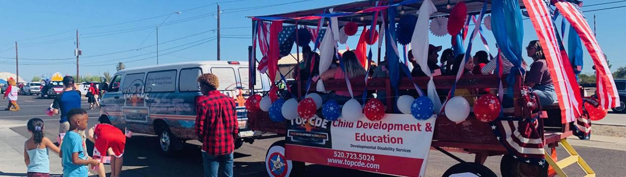 A group of adults sit inside a full-sized wagon with canopy. The wagon is decorated with red, white and blue streamers, stars and balloons.