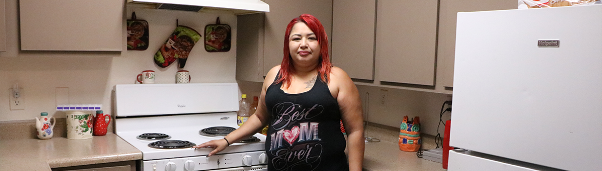 """A woman wearing a """"best mom ever"""" tank top and shorts stands next to the stove in a kitchen"""