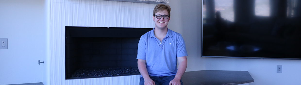 young man dressed in jeans and a polo shirt, sits on the ledge of his living room fireplace