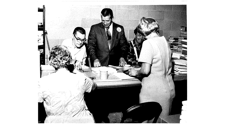 office workers stand around a man sitting at a desk