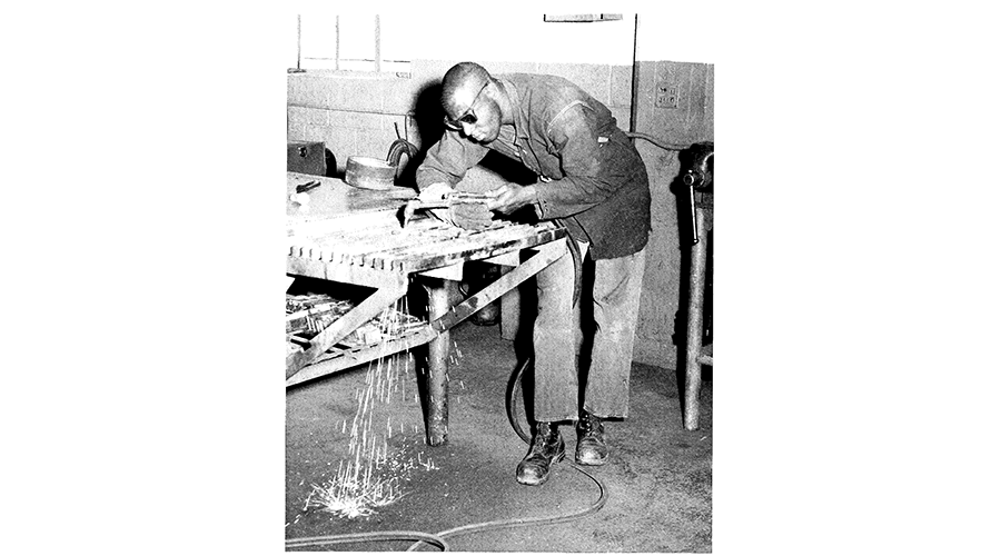 a man leans over a welding machine