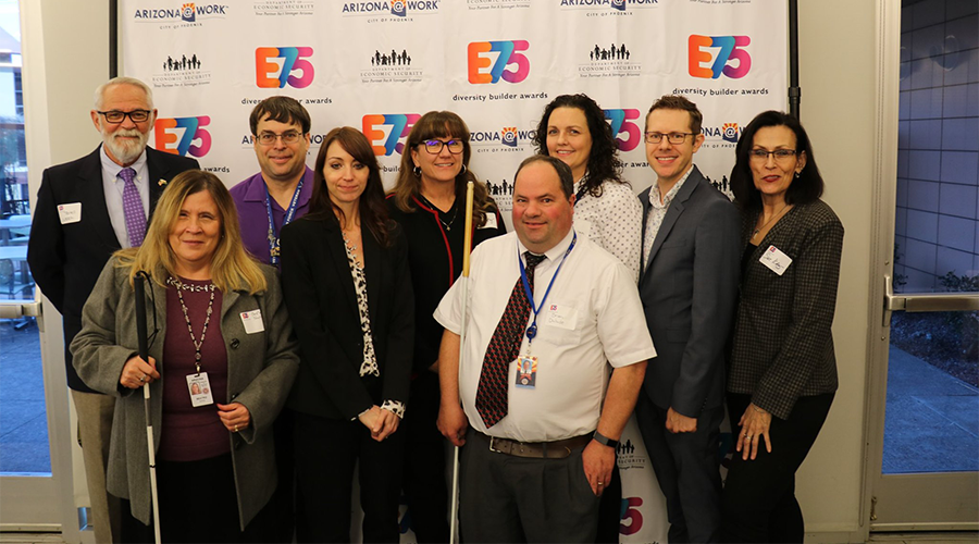 a group of business professionals stand before a backdrop that reads E75