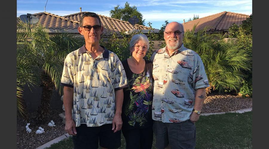 an older man wearing glasses stands next to an older man and woman in a backyard garden area.