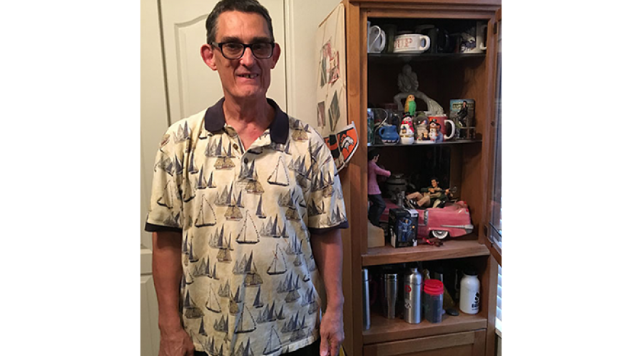 an older man wearing glasses is smiling; he is standing next to a wooden bookcase