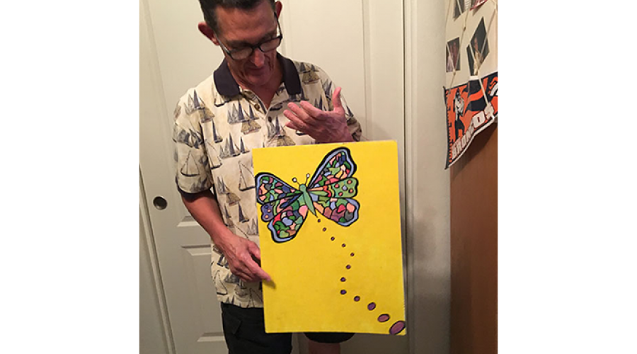 an older man holds a large bright and colorful drawing of a butterfly