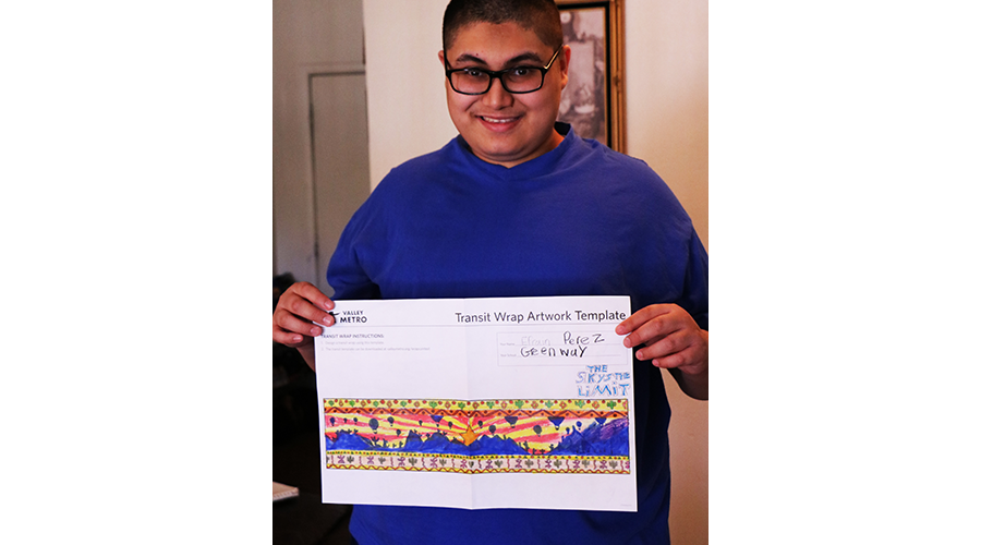 a teenage boy smiles; he is holding up a drawing of a colorful desert scene