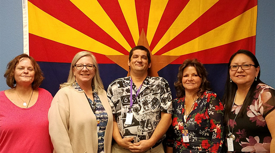 Four women and a man stand in a row in front of the Arizona flag.
