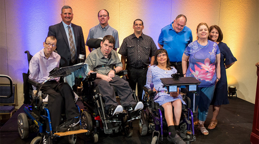 Six men and three women pose together for a picture. There are three individuals using wheel chairs in the front row, while the other participants stand in a row behind them.