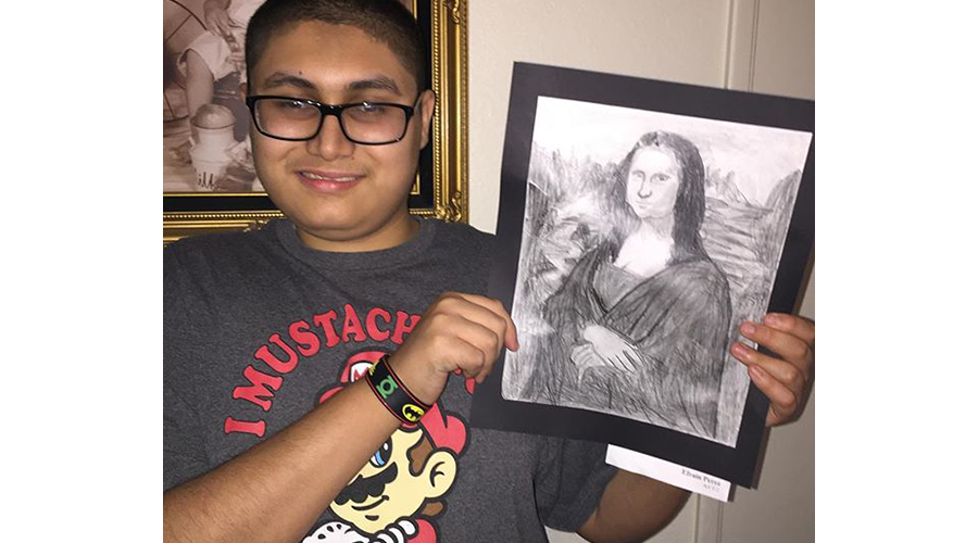 a teenage boy smiles; he is holding up a drawing of the Mona Lisa