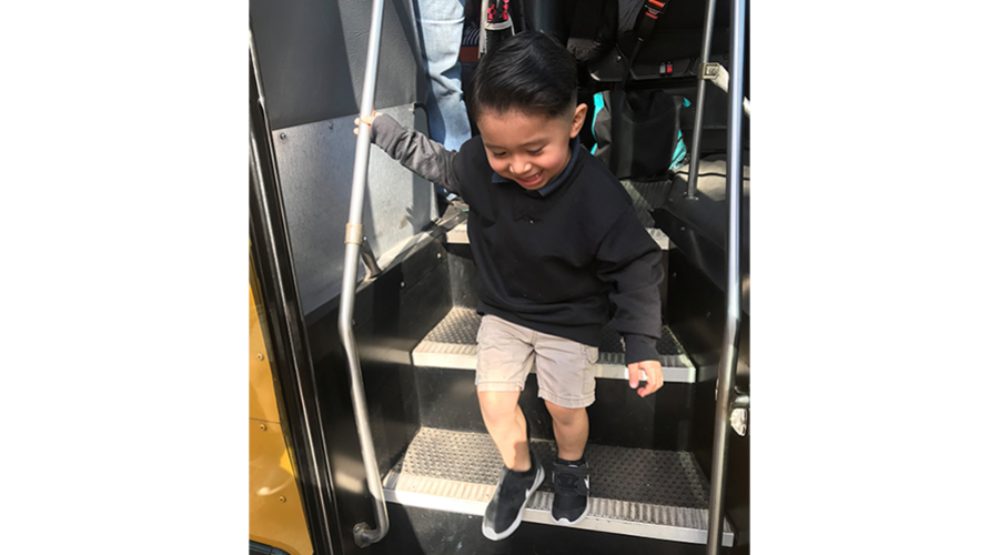 Toddler boy takes a step off the school bus on his first day of school.