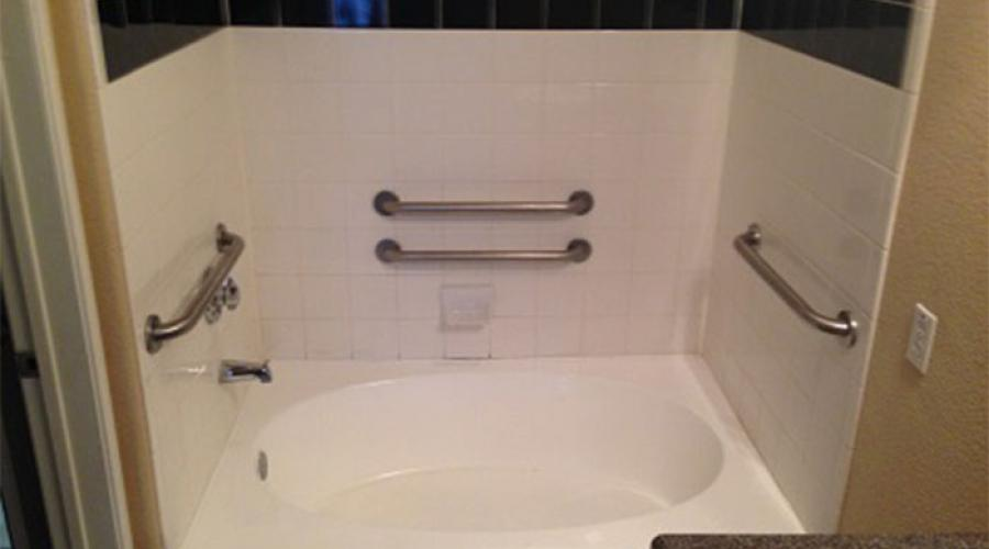 A bathtub with handles to the left and right, and behind.
