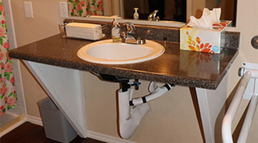 A bathroom sink in front of a mirror, without cabinets underneath so it is more accessible.