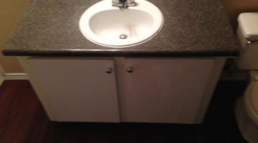 A bathroom sink with cabinets underneath