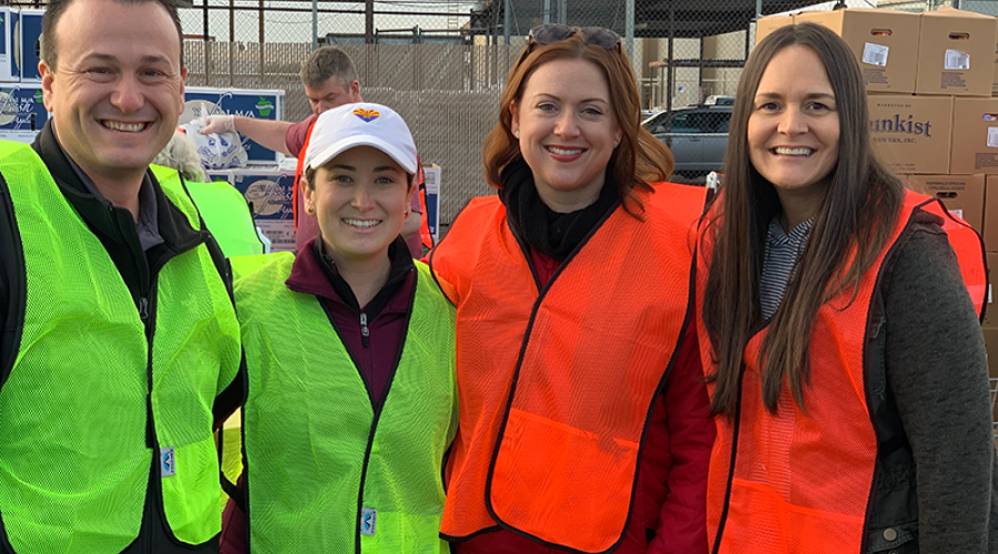 four people wearing neon green or orange vests pose for a photo