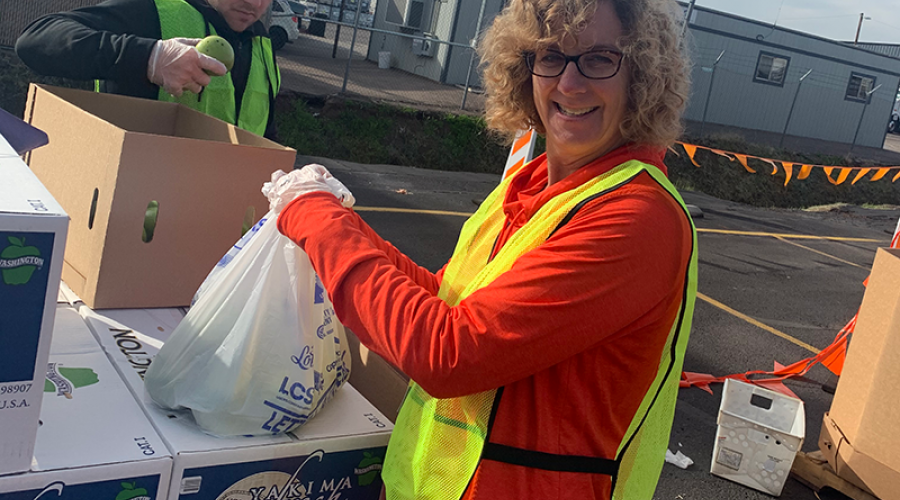 a woman wearing a bright yellow vest is placing a plastic bag on top of a stack of cardboard boxes