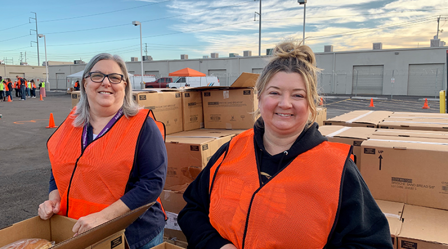 two women wearing bright orange vests are surrounded by cardboard boxes