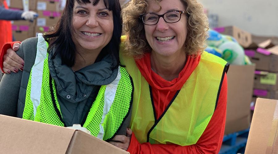 two women wearing bright yellow vests smile, posing for a photo