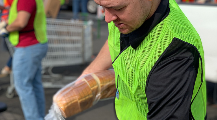 a man wearing a bright green vest is holding a loaf of bread
