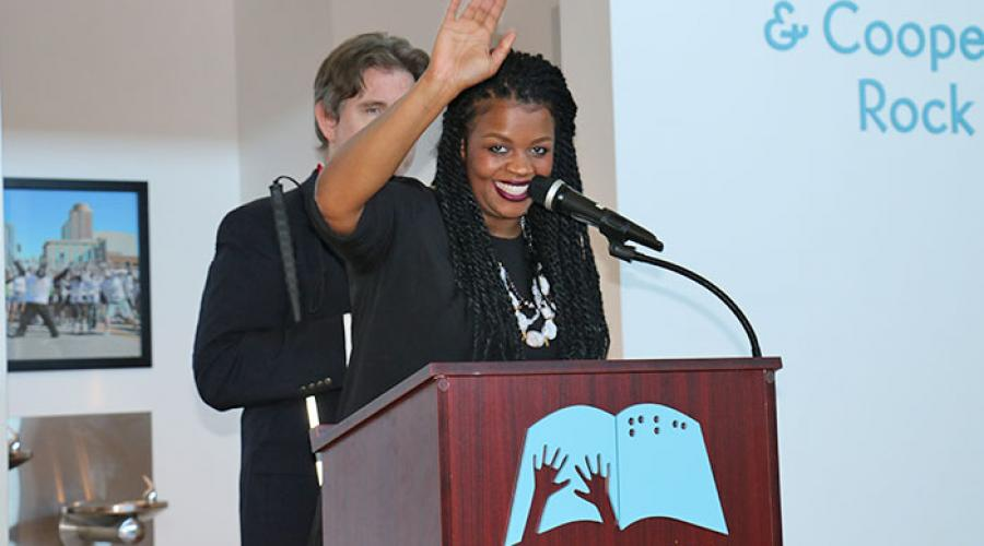 a woman stands behind a podium waving at the audience