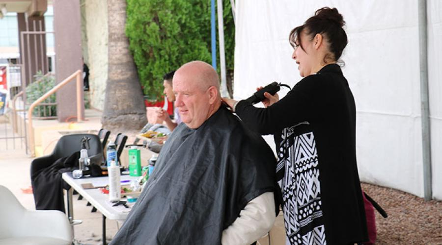 a woman uses an electric razor to give a man a haircut