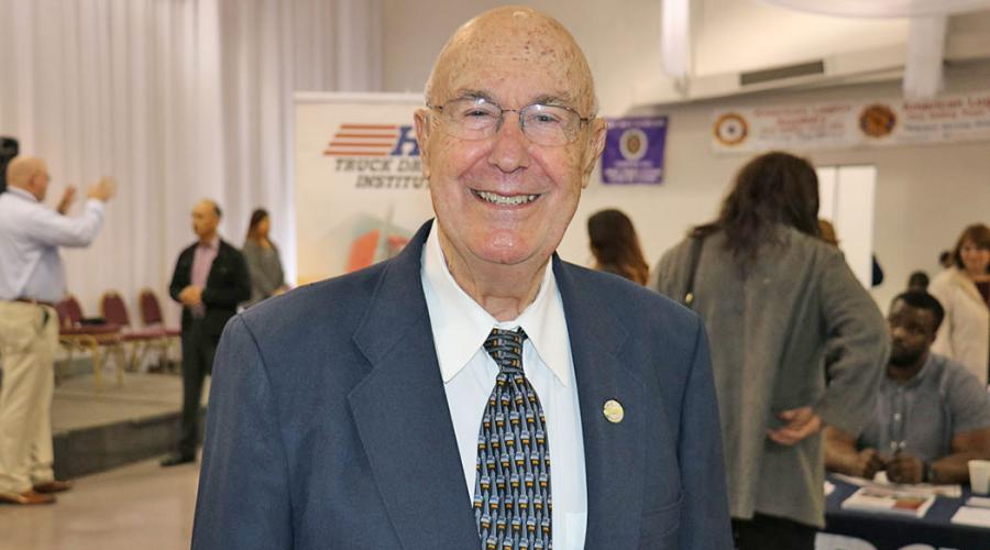 an older man wearing a business suit smiles for the camera