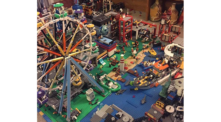 a city scape made of Legos toy blocks; a toy ferris wheel stands near the make-believe harbor
