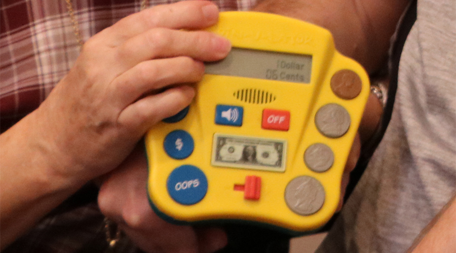a hand holds up a learning device with a display area and buttons that resemble coins