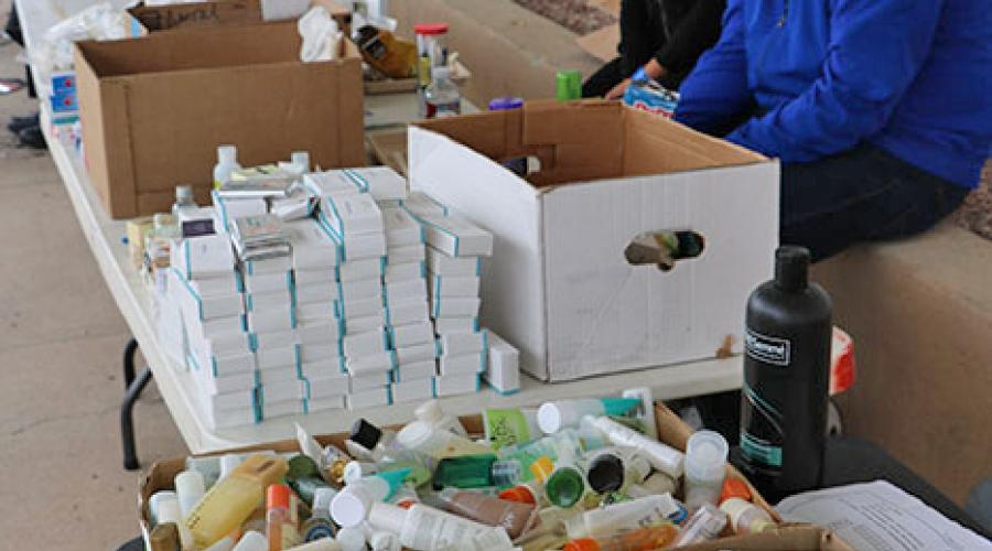 free hygiene products sit on table tops and in cardboard boxes