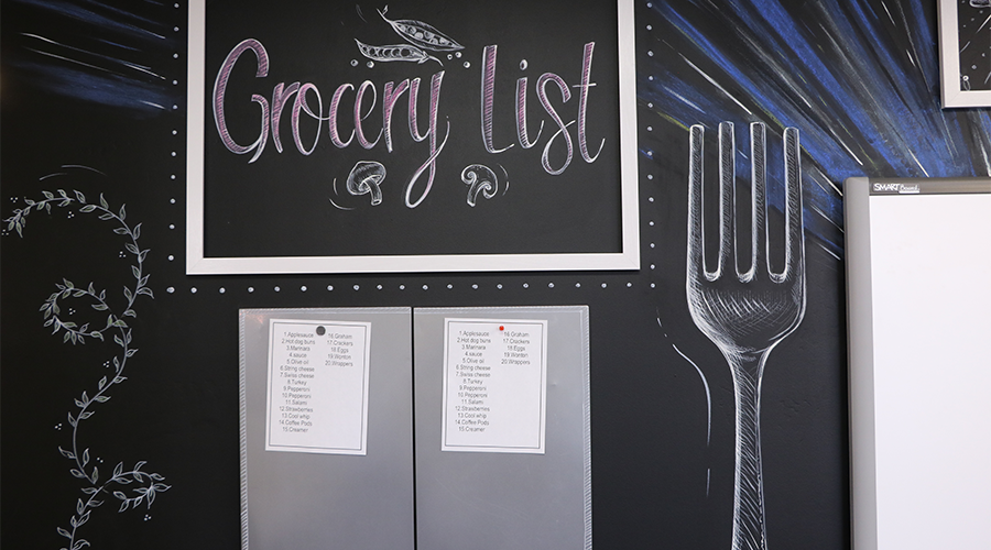 """Two grocery lists are tacked onto a display wall that replicates a black board.  The wall features a chalk-like drawing of a fork and a sign that reads """"Grocery List."""""""