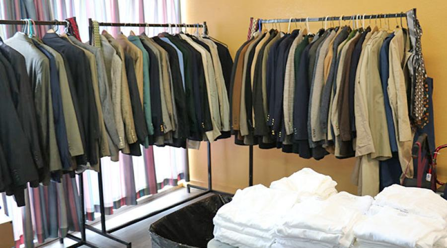 men's jackets fill three clothing racks, a table holds stacks of mens undershirts