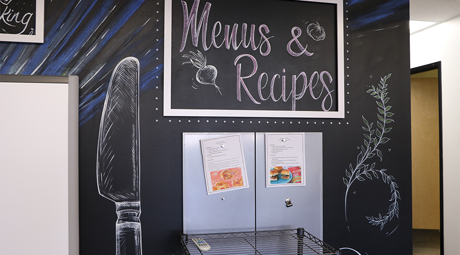 "Two menus are tacked onto a display wall that replicates a black board.  The wall features a chalk-like drawing of a knife and a sign that reads ""Menus & Recipes."""
