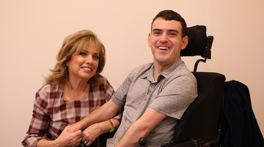 a woman in a plaid blouse sits next to a 20-year old man who is in a wheel chair