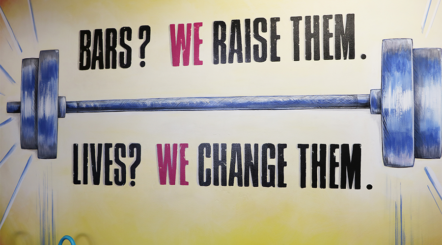 "A graphic image of barbells is painted onto a yellow wall.  Above the drawing are the words, ""Bars?  We raise them.""  Below the drawing are the words, ""Lives?  We change them."""