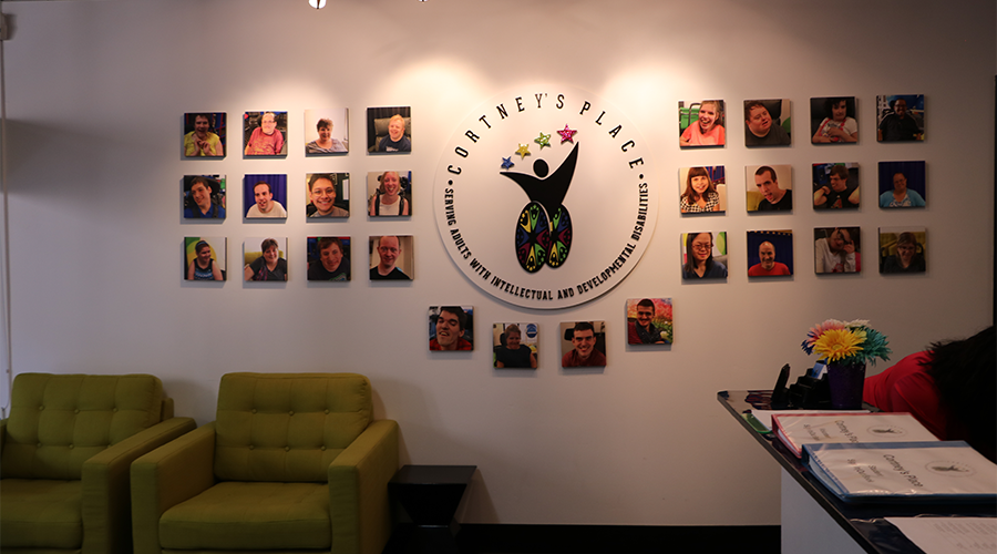 A lobby wall displays the Cortney's Place logo, which is surrounded by head shots of various students.