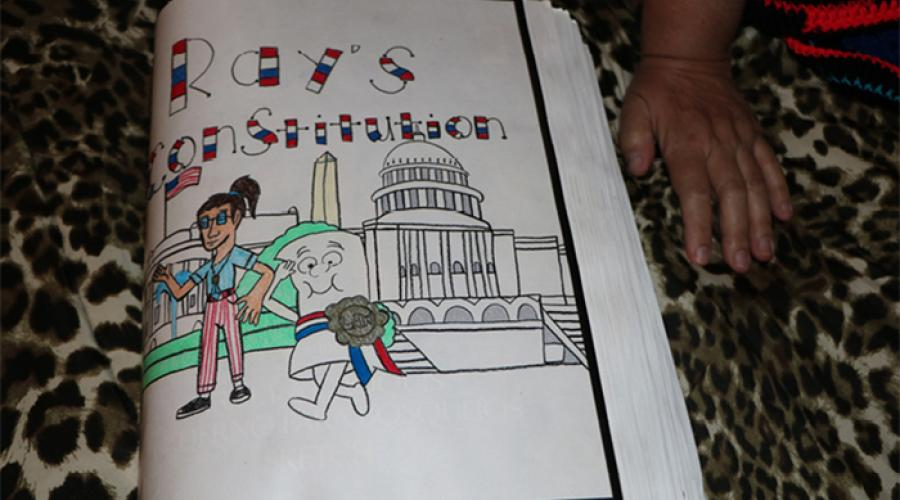 "A drawing of cartoon figures and the White House; the words "" Ray's Constitution"" display at the top"