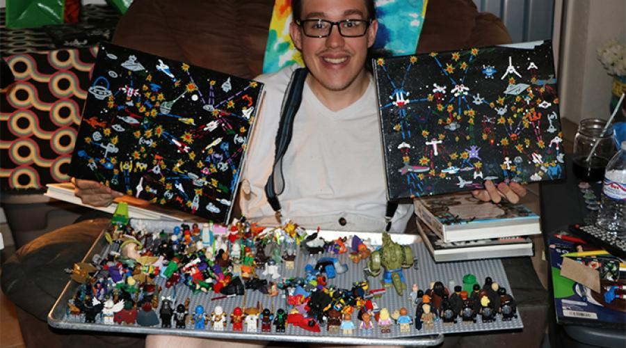 A young man sits on a sofa, holding up two paintings; a tray holding various Lego creations rests on his legs.