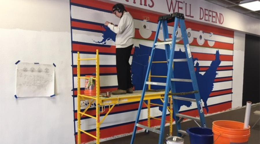 "Man standing on scaffold paints mural that includes a map of the United States; the words ""This we'll defend"" display at the top"