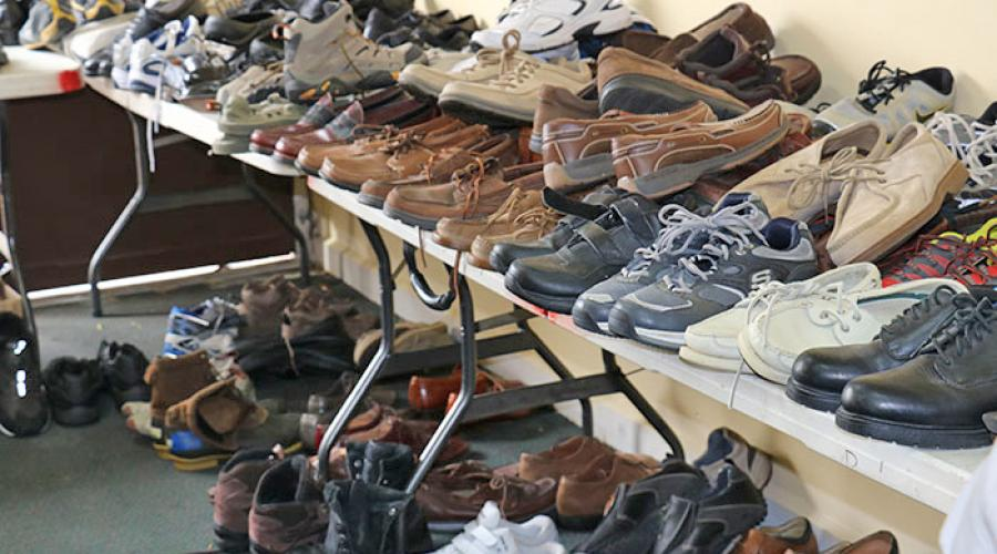 rows of mens shoes sit on top and underneath tables