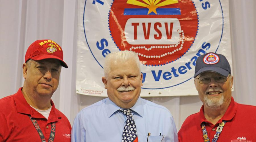 three men stand before a banner that reads tucson veterans serving veterans
