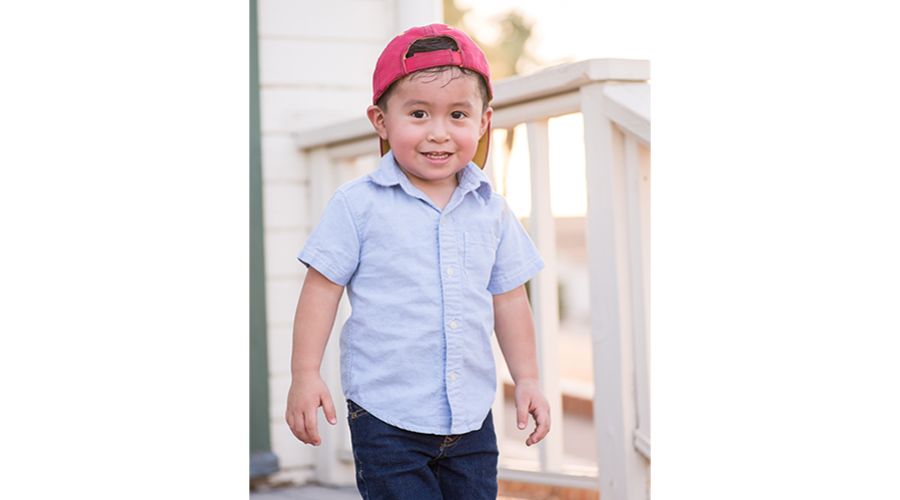 Young boy wearing a red baseball cap turned backwards, stands on a porch and smiles at the camera.