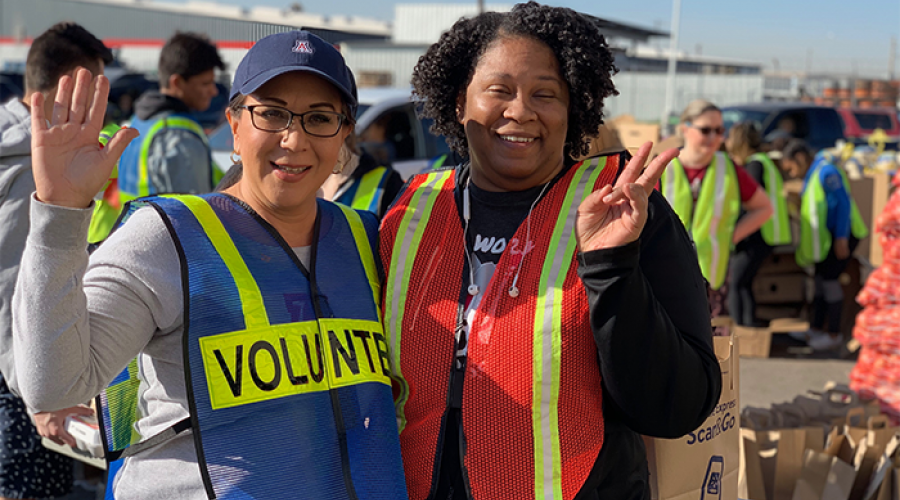 Two DES Volunteers at St. Mary's Food Bank waving