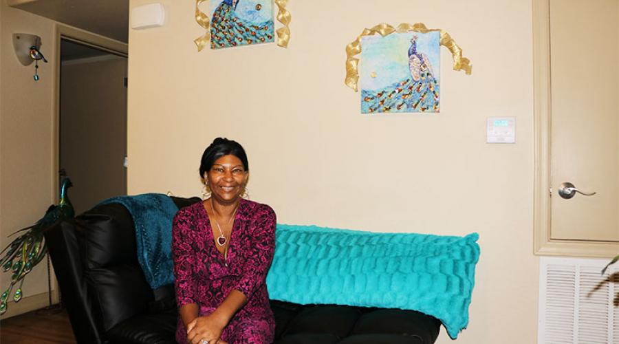 a woman sits on a sofa, smiling for the camera