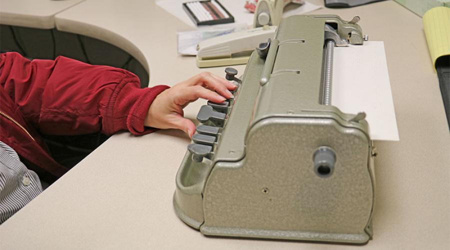 Woman's hand on Braille Typewriter