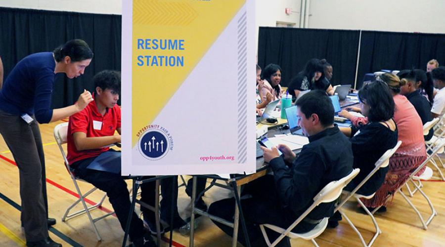 young job seekers work on computers to create resumes