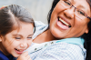 woman wearing glasses is hugging young girl