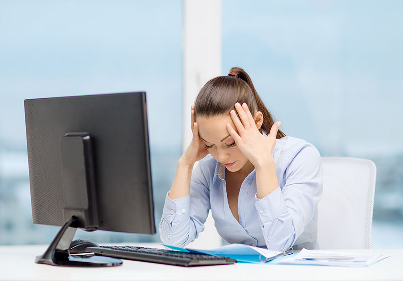 woman sits at desk holding her head in her hands